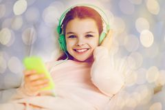 Girl with headphones listening to music in bed. People, children and technology concept - happy smiling girl lying awake with smartphone and headphones in bed Stock Photography