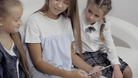 People, children, technology, friends and friendship concept - happy three little girls with tablet pc computer sitting. People, children, technology, friends stock footage
