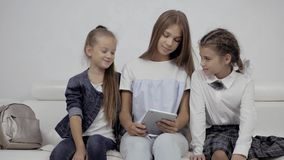 People, children, technology, friends and friendship concept - happy three little girls with tablet pc computer sitting. People, children, technology, friends stock video