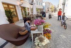People with children walking on historical street with outdoor flower shop Royalty Free Stock Photo
