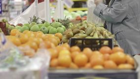 People choose fruit in store. Different fruits lie on the counter for choice stock footage