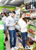 People choosing wine in a shop. Different people choosing wine in a supermarket spirits section Stock Images