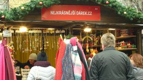 Brno, Czech Republic, December 21, 2018: People at the Christmas advent market stall at the square, sale of gifts of. People at the Christmas advent market stall stock footage