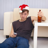 People in christmas hat sits on a floor with beer Royalty Free Stock Image