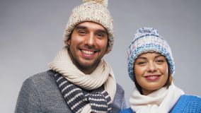 Happy couple in winter clothes. People, christmas and winter clothes concept - happy couple in knitted hats and scarves over grey background stock footage