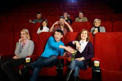 People in a cinema. Group of young people watching movie in cinema royalty free stock image