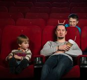 People in cinema. Man with boy in cinema with funny guy behind them royalty free stock image