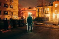 People circled the glowing wire at night in the courtyard. Stock Photos
