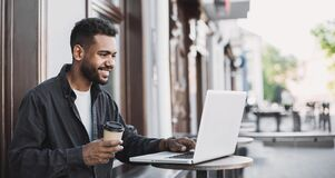 Free People City Lifestyle Young Man Sitting In A Cafe Using His Laptop Computer Typing Keyboard Online Outside Stock Photo - 172869000