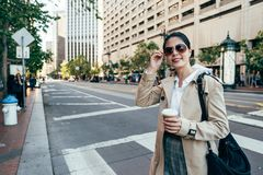 People city urban lifestyle in san francisco. Asian woman in sunglasses smiling face camera. young elegant office lady drinking cocoa walking on zebra crossing royalty free stock image