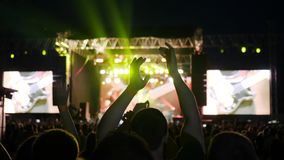 People clap their hands, night rock concert in open air, slow motion many lights on stage
