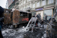People clean the winter street with ice-covered transport burned in fights with police squads Royalty Free Stock Photos