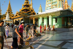 People cleaning with brooms the area of the Shwedagon Pagoda in Stock Image