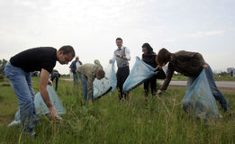 People cleaning grassland Stock Images