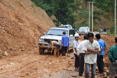 People clear a road because of landslide. NORTHERN LAOS - AUGUST 14: People clear a road because of landslide on August 14, 2012 in Northern Laos. Landslides are Royalty Free Stock Photography