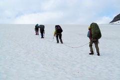 People climbers, climbing snow summit, rocky mountain peaks and glacier in Norway Stock Photo