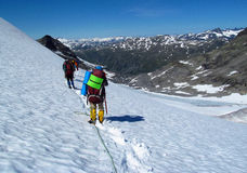 People climbers, climbing snow summit, rocky mountain peaks and glacier in Norway Royalty Free Stock Image