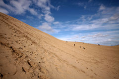People Climbing Desert Dunes Stock Photo