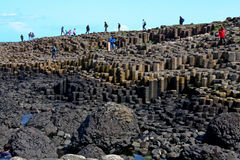 People climbing Giants Causeway and Cliffs, Northern Ireland. Giants Causeway, unique geological formation of rocks and cliffs in Antrim County, Northern Ireland stock photo