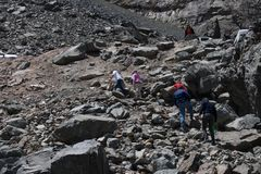 People climbing a mountain with many rocks stock image