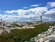 People climbing rocks at famous Peggy's Cove lighthouse, Canada Stock Photography