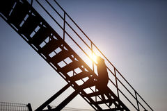 People climbing stairs in sunset Stock Images