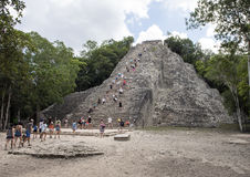 People climbing up an down the Nohoch Mul Pyramid in the Coba ruins stock photography
