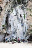 People climbing up a steep limestone cliffs Stock Photo