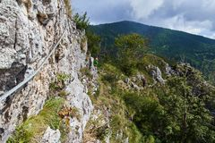 Peopl climbing on via ferrata. People climbing on via ferrata in the mountains Stock Photo