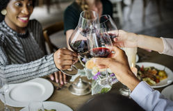 People Clinging Wine Glasses Together in Restaurant stock photo
