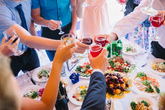 People clink glasses of wine at the holiday party Stock Images
