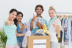 People with clothes donation gesturing thumbs up Stock Images