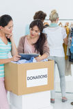 People with clothes donation while using digital tablet Royalty Free Stock Photography