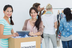 People with clothes donation while using digital tablet Stock Photography
