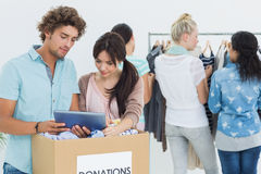 People with clothes donation while using digital tablet Stock Photo