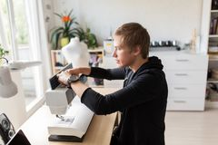 Fashion designer with sewing machine at studio Stock Images