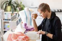 Fashion designer with coffee and book at studio Royalty Free Stock Photo
