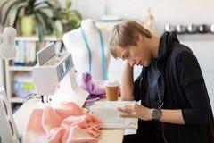 Fashion designer reading book at studio Stock Images