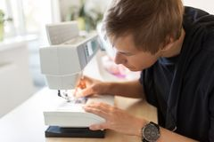 Fashion designer with sewing machine at studio Stock Photo