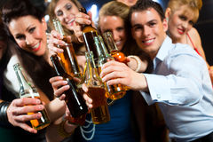 People in club or bar drinking beer. Young people in club or bar drinking beer out of a beer bottle and have fun stock image