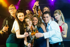 People in club or bar drinking beer. Young people in club or bar drinking beer out of a beer bottle and have fun stock photo