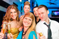 People in club or bar drinking champagne. Young people in club or bar drinking champagne and having fun; all are looking into the camera stock photo