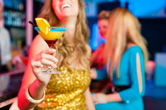 People in club or bar drinking cocktails. Young women in club or bar drinking cocktails and having fun royalty free stock photos