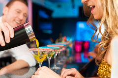 People in club or bar drinking cocktails. Young people in club or bar drinking cocktails and having fun; the barkeeper is mixing drinks stock photography