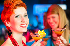 People in club or bar drinking cocktails. Young women in club or bar drinking cocktails and having fun royalty free stock photography