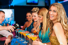 People in club or bar drinking cocktails. Young people in club or bar drinking cocktails and having fun; the barkeeper is mixing drinks stock photos