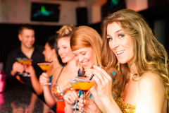 People in club or bar drinking cocktails. Young people in club or bar drinking cocktails and having fun royalty free stock photography