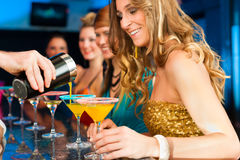 People in club or bar drinking cocktails. Young people in club or bar drinking cocktails and having fun; the barkeeper is mixing drinks royalty free stock images