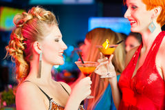 People in club or bar drinking cocktails Stock Images