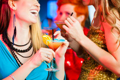 People in club or bar drinking cocktails. Young women in club or bar drinking cocktails and having fun stock photo